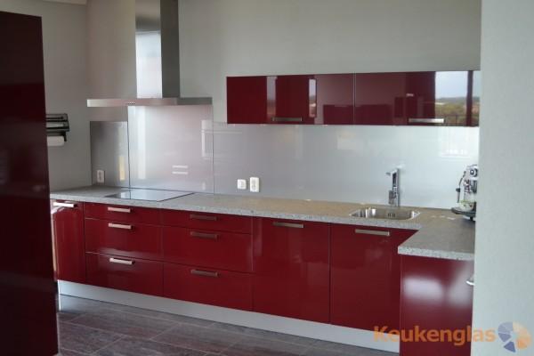 rode keuken met witte glaswand