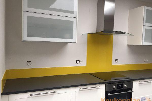Gele keuken achterwand van glas