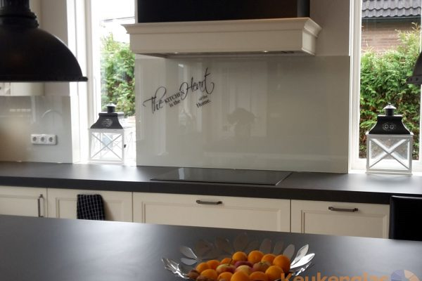 witte-glasplaat-achter-fornuis-met-tekst-the-kitchen-is-the-heart-of-the-home